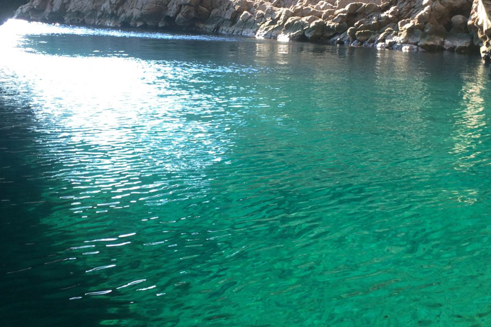 """the mystical """"Gangara Hollow,"""" a cave filled with cobalt blue waters"""